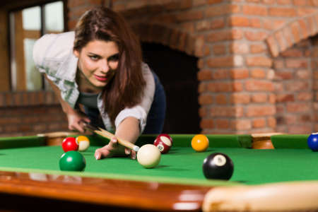 Woman playing billiards Banque d'images