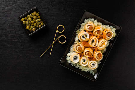Rolled herring in olive, served with onions. Perfect for vodka. Black stone try on background.  Top view. Stock Photo