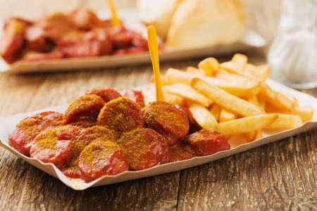 Traditional German currywurst, served with chips on disposable paper tray. Wooden table as  background. 版權商用圖片