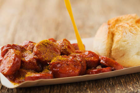 Traditional German currywurst, served on disposable paper tray with a fresh bun. Wooden table background.
