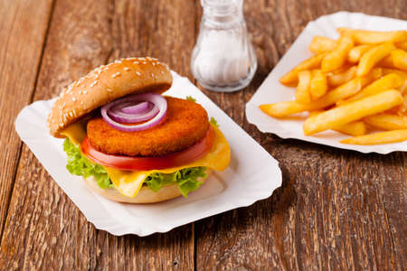 Delicious fish burgerserved with fresh french fries, servwed on a paper try.