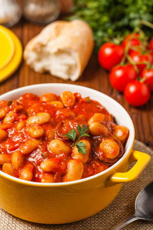 Baked beans in tomato sauce served in yellow, clay bowls. Front view.
