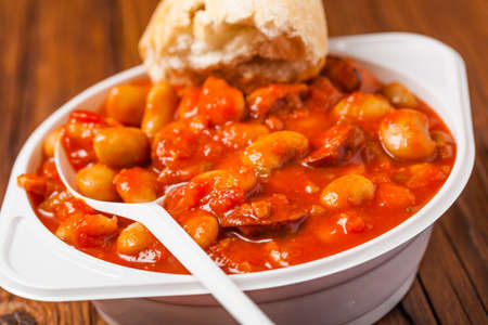 molasses: Baked beans in tomato sauce served in plastic cups. Front view. Stock Photo