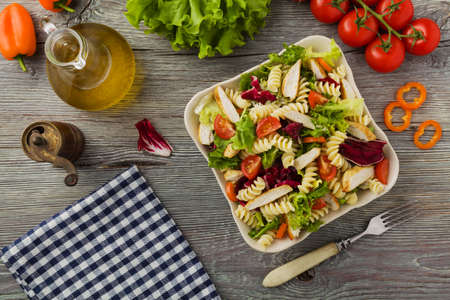 macarrones: Delicious pasta salad with green lettuce, tomatoes and roasted chicken. Foto de archivo