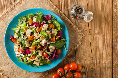 두부, 토마토, 호두 wÅ,aoskimi 맛 샐러드, 발사믹 식초의 소스와 함께 이슬비와 블루 접시에 제공합니다. 평면도.