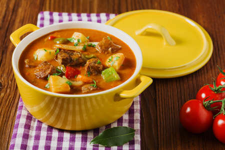 Beef stew served with cooked potatoes in a yellow little pot on a wooden background.