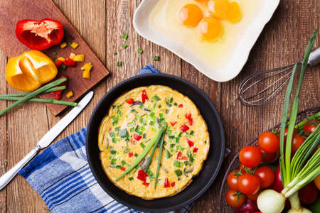 Delicious omelette with vegetables in a pan.  Reklamní fotografie