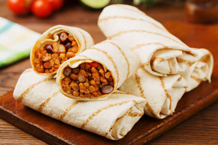 Burritos wraps with meat, beans and vegetables on wooden board Stock Photo