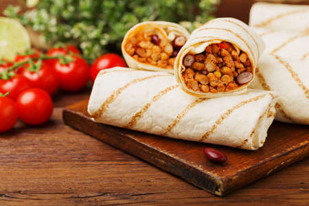 filled roll: Burritos wraps with meat, beans and vegetables on wooden board Stock Photo