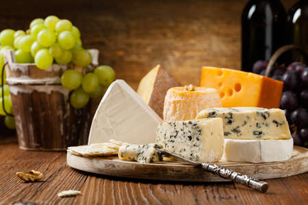 Mix cheese on wooden board with grapes. Front view.