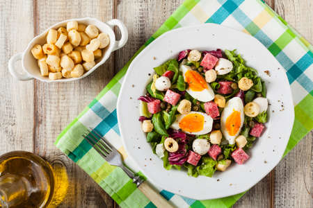 Delicious Italian salad with salami, egg, crostini and mozzarella. Top view. Banco de Imagens