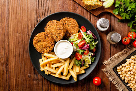 Serving of falafel and chips served on a black plate with sauce. Top view. Wooden board background.