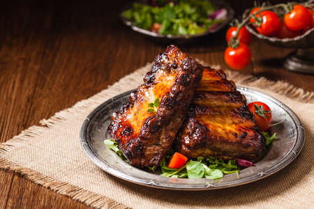 Roasted ribs, served on an old plate. Fron view. Dark or balck background. Stock Photo