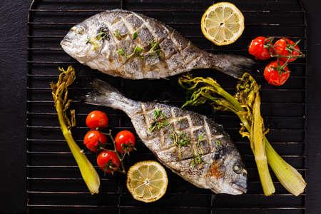 구운 생선 구이, 구운 채소와 레몬을 곁들여서 먹습니다. 전면보기.