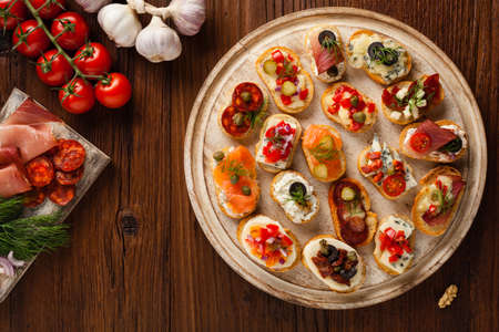 Crostini with different toppings on wooden background. Delicious appetizers. Top view.
