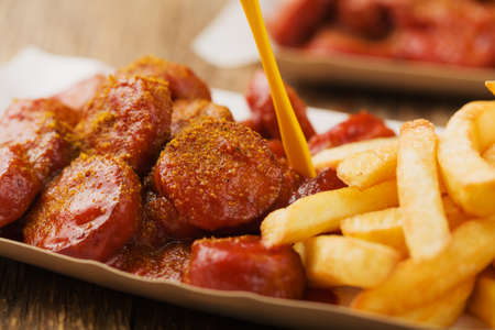 Traditional German currywurst, served with chips on disposable paper tray. Wooden table as  background. Zdjęcie Seryjne
