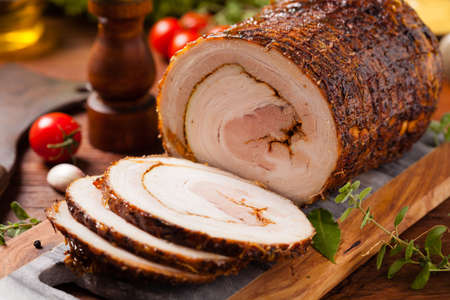 Rolled, roasted pork belly. Front view.