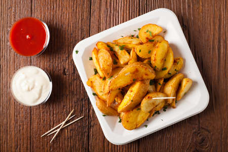 dipping: Traditional Spanish baked potato with hot pepper chili. Bravas dip. Top view Stock Photo