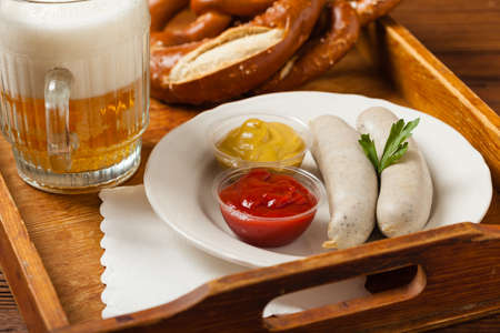 Boiled white sausages, served with beer and pretzels. Perfect for Octoberfest. Natural wooden background. Front view. Stock Photo