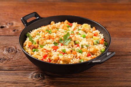 Fried rice with chicken. Prepared and served in a wok. Natural wood in the background. Front view.