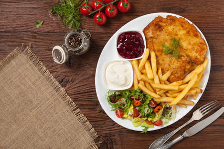 Chicken schnitzel, served with fries and salad. Natural wooden background. Top view.
