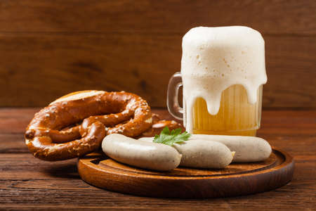 Boiled white sausages, served with beer and pretzels. Perfect for Octoberfest. Natural wooden background. Front view. Фото со стока