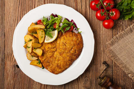 Chicken schnitzel, served with roasted potatoes and salad. Top view. Natural wooden background Stock Photo