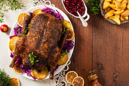 Baked whole duck, served with apples, red cabbage, oranges and roasted fritters. Natural wooden table in the background. Top view.