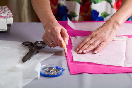 Naaiatelier. De naaideken voorbereiden. Op basis van het materiaal. De kleermaker tekent een te snijden patroon.