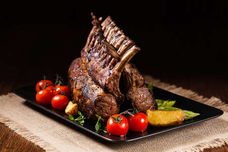 Baked lamb loin, served with asparagus. Dark background. Stockfoto
