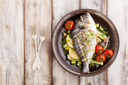 gilthead: Baked whole fish, served with roasted vegetables and lemon. Top view.