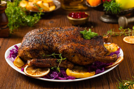 Baked whole duck, served with apples, red cabbage, oranges and roasted fritters. Natural wooden table in the background. Front view.