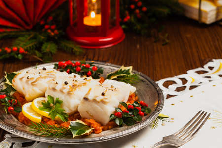 Christmas fish. Roasted cod pieces, served in vegetable sauce. Xmas styling. Front view. Foto de archivo