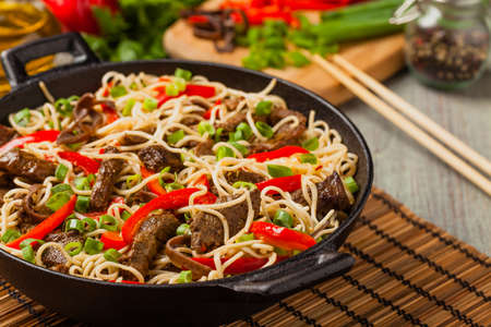 Chinese pasta with beef. Prepared in wok. Wooden background. Front view.