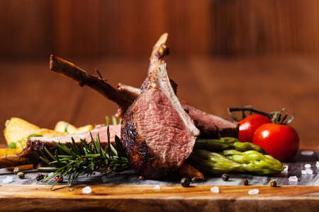 Baked lamb loin, served with asparagus. Dark background. Stock Photo