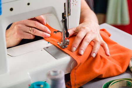 Sewing workshop. Stapling the material on the machine.