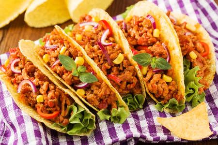 Několik kusů tacos s masem a zeleninou na dřevěné desce