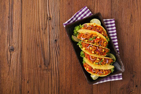 Few portion of tacos with meat and vegetables on wooden board Stock Photo