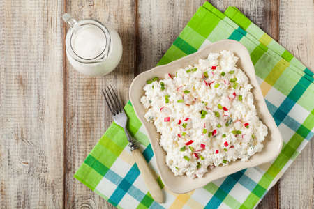 Fresh cottage cheese, served with fresh vegetables and cream. Top view. Foto de archivo