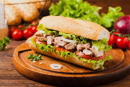 Delicious tuna sandwich, served with lettuce, tomato and onion. Natural wood in the background. Front view. Stock Photo