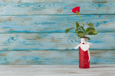 Valentines Day. Rose in a vase on blue wooden background.