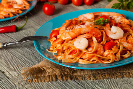 Pasta with shrimps. Wooden background. Front view. Stock Photo