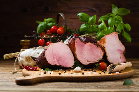 Smoked pork on wooden board. Different types of meat.