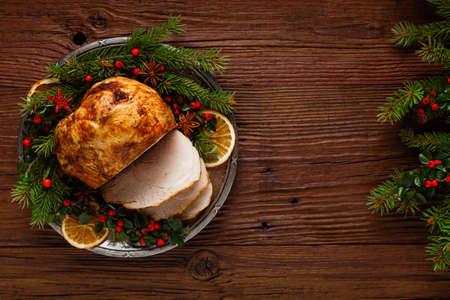 Jambon au four de Noël, servi dans l'ancienne assiette. Brindilles d'épinette tout autour. Vue de dessus. Banque d'images