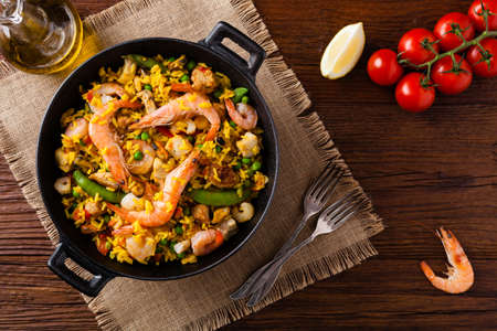Traditional Spanish paella with seafood and chicken. Prepared in wook. Top view. Stock Photo