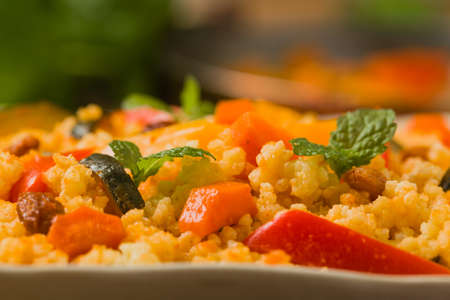 Millet with vegetables and raisins. Front view. Close up.