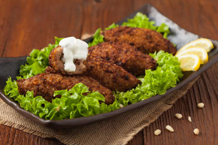 Traditional arabic kibbeh with lamb and pine nuts. Front view. Natural wooden background.