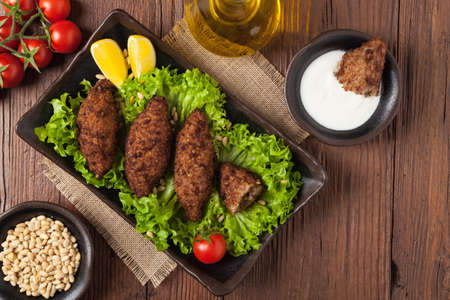 Traditional arabic kibbeh with lamb and pine nuts. Top view. Natural wooden background. Imagens