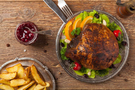Baked ham, served on an old plate. Natural wooden background. Top view. Stock Photo