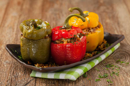 Colorful baked with cheese, stuffed peppers with rice and minced meat. Front view. Natural wooden background.